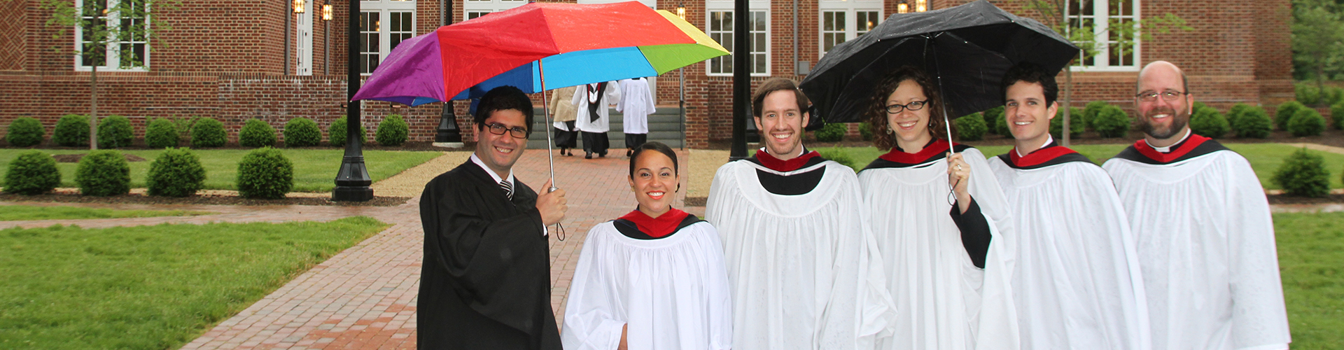 Staff standing outside under umbrellas