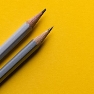 Two pencils sitting on a yellow background